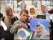 Palestinians hold pictures of Yasser Arafat in Ramallah