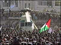 Mourners surge around the helicopter carrying Yasser Arafat's coffin