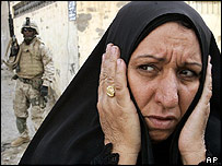 Woman holds her head as US soldier walks in Falluja street