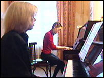 Anna playing the piano with her music teacher