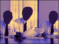 Three people sitting at a boardroom table