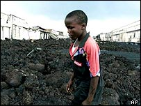 A boy walks through lava rocks in Goma