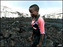 A boy walks through lava rocks in Goma