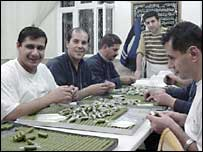 Men wrapping pistachio sweets for the end of Ramadan holiday