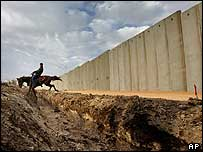 A Palestinian canters past the barrier Israel is building in Israel and the Occupied Territories