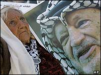 A woman next to a poster of the late Palestinian leader Yasser Arafat