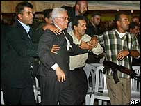 Bodyguards hustle Mahmoud Abbas away after shots were fired nearby on Sunday