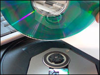 CD being placed in computer drive, BBC