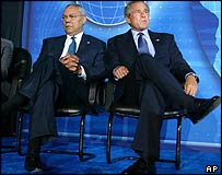 Colin Powell and George Bush facing away from each other