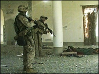 Two armed US marines point a rifle at a wounded insurgent