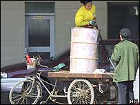 An attendant pumps petrol into a drum on the back of a tricycle at a petrol station in Beijing (26/10/04)