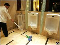 Trabajador de limpieza chino aseando inodoros en la Cumbre Mundial del Inodoro.