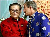 US President Bush, right, in a traditional Chinese coat, talks to Chinese President Jiang Zemin in October 2001
