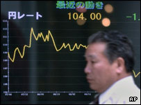 Man walking past electronic screen showing dollar's slide against the yen