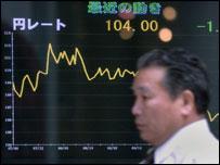 Un hombre pasa frente a una pantalla que muestra la caída del dólar frente al yen.