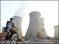 A man cycling past a state steel mill in Beijing, China