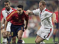 England's Nicky Butt, right, and Ashley Cole, left, duel for the ball with Spanish midfielder Xavi