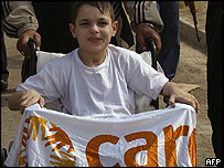 A disabled Iraqi boy holding up a banner in support of Margaret Hassan
