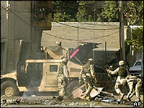 US troops search through rubble of a Humvee destroyed in a rocket attack which killed several soldiers in Baghdad's Adhamiya district