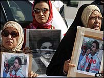 Bahraini women holding pictures of human rights activist Abdul Hadi al-Khawaja outside the courtroom on Sunday
