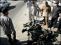 Iraqis gather around a burnt car in Baghdad on 21 November 2004.