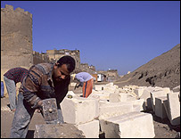 Stone masons working between old city wall and the park area