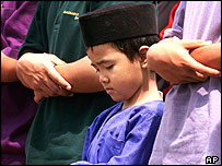 A Malay boy joins other elder Muslims in offering a prayer during the fasting month of Ramadan at a mosque in Kuala Lumpur, Friday, Nov. 8, 2002.