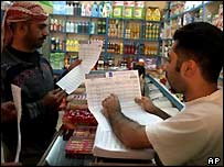 A shopkeeper explains how to fill in voter registration forms to a customer in Baghdad, 23 November 2004