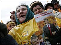 Ukrainian demonstrators wearing orange raincoats and holding Yushchenko posters chant anti-government slogans, 23 November 2004