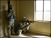 Marine aims his machinegun through window during Falluja assault - photo Robbie Wright