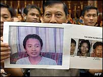 Indonesian police officer holds up pictures of suspects (24/11/04)