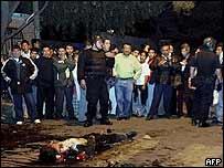 Un grupo de personas observa el cuerpo de uno de los agentes linchados.