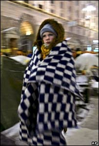 A Ukrainian girl wrapped in blankets to keep warm walks through the tent camp occupied by supporters of opposition candidate Viktor Yushchenko in Kiev