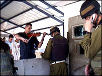 Palestinian plays violin at Israeli checkpoint (image credit: Horit Herman Peled)