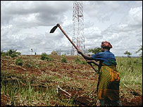 A woman works in a field close to a new mobile base station