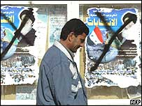 A man walks past election posters in Baghdad