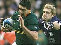 South Africa's Jaque Fourie is pursued by Scotland's Sean Lamont