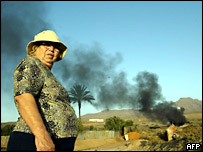 A farmer in Fuerteventura burns tyres to deter locusts from eating her crops