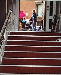 Photo of wheelchair user at top of staircase