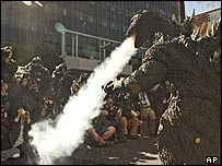 Godzilla breathing smoke on TV crews
