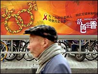 A man walks past a Chinese government-sponsored poster on HIV/Aids