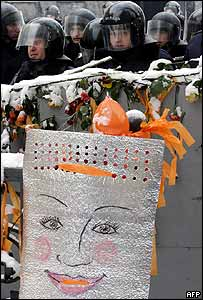 A police shield is decorated with the opposition's trademark orange in front of a police cordon