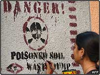 An Indian environmental activist paints a protest sign against the wall of the Union Carbide pesticide plant in Bhopal, 1 December 2004