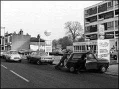 Two men push car to petrol station - Hampton Hill, London, 1973