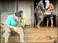 A villager cries as the body of a flood victim is recovered in Real