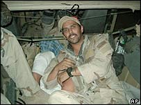 A photograph which appears to show a member of the US military in a truck with Iraqi prisoners