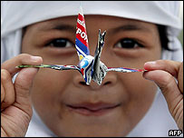 Thai-Muslim student in Pattani province displays an origami bird she collected after the air drop