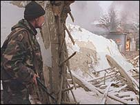 Soldier stands next to a ruined building in Grozny
