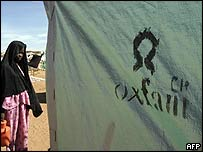 A girl waits outside a tent set up by the aid organisation Oxfam in a refugee camp in Darfur, Sudan