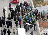 Workers and police officers stand outside a traditional courtyard housing area in Beijing 15/12/04